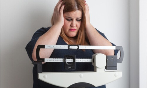A woman worried about her increasing weight. She needs to find ways on how to prevent obesity.